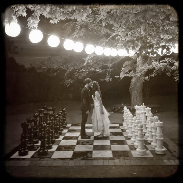 Bride and groom kissing on giant chess board - Picture by Jonas Peterson Photography