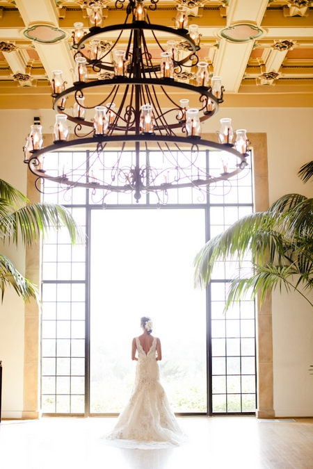 Bride standing in front of large glass window - Picture by Allyson Magda Photography