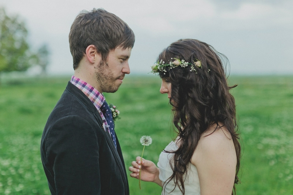 Bride holding dandelion facing groom - Picture by Jonas Peterson Photography