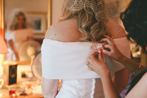 Doing up back of bride's wedding dress - Picture by McKinley-Rodgers Photography