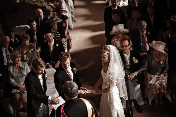 Bride and groom holding hands during wedding ceremony - Picture by Archibald Photography