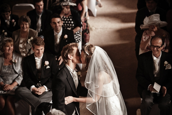 Bride and groom kissing during wedding ceremony - Picture by Archibald Photography