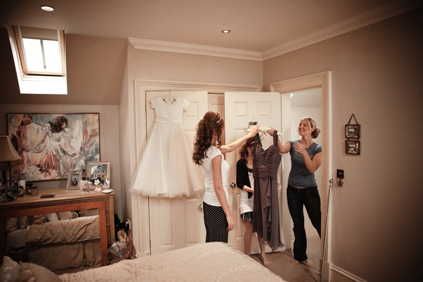 Bride handing bridesmaid her dress - Picture by Archibald Photography