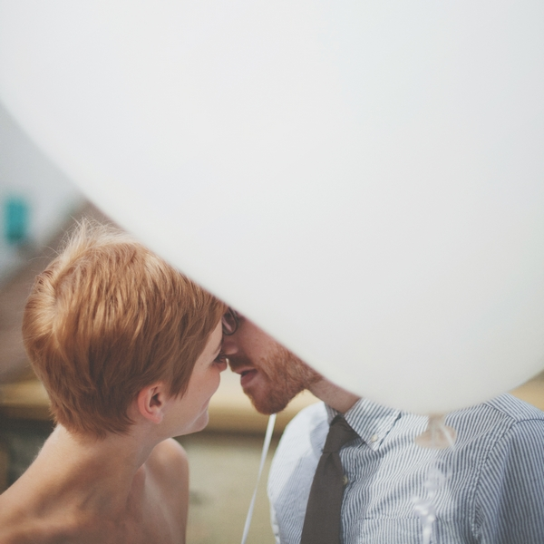 Bride and groom kissing behind balloon - Picture by Josh Dookhie Photography
