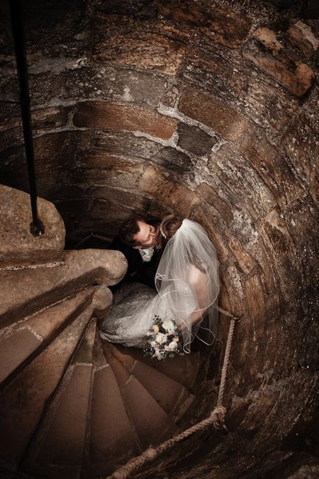 Bride and groom on steps at Dirleton Castle - Picture by Archibald Photography