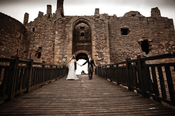 Bride and groom holding hands as they walk across bridge at Dirleton Castle - Picture by Archibald Photography