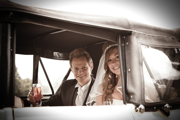 Bride and groom in back of wedding car - Picture by Archibald Photography