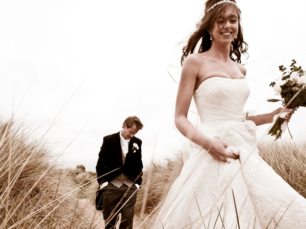 Bride and groom walking through long grass - Picture by Archibald Photography