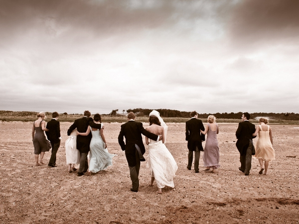Wedding party walking across beach - Picture by Archibald Photography