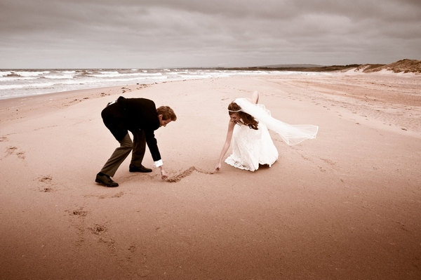 Bride and groom drawing heart in the sand - Picture by Archibald Photography