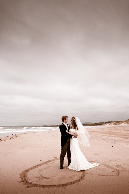 Bride and groom standing on heart in the sand on beach - Picture by Archibald Photography