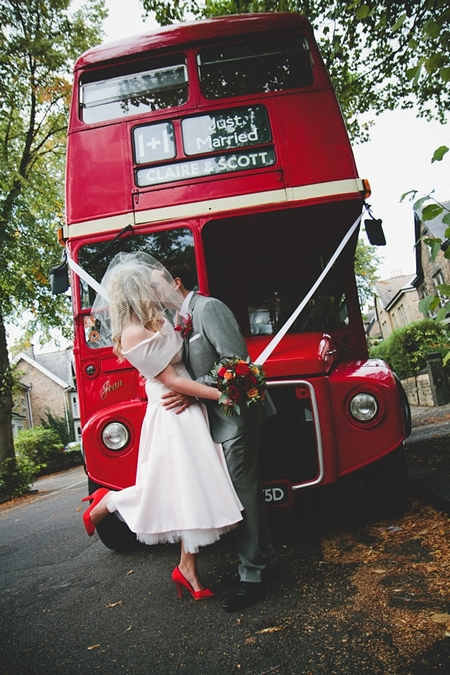 Bride and groom kissing in front of red wedding bus - Picture by McKinley-Rodgers Photography