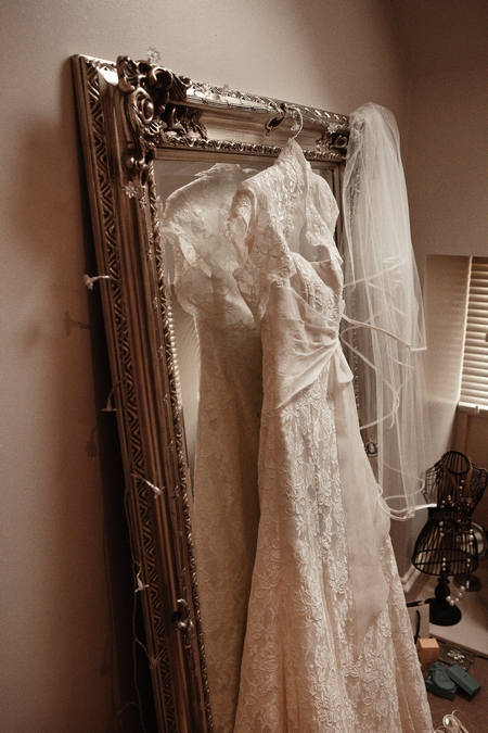 Lace wedding dress hanging on mirror - Picture by Archibald Photography