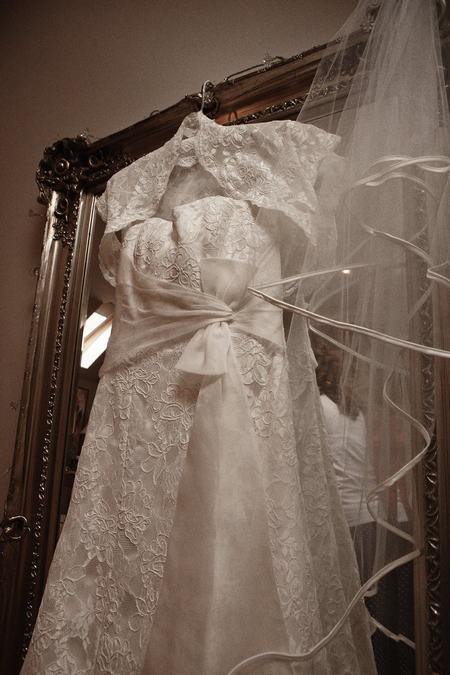 Front of lace wedding dress hanging on mirror - Picture by Archibald Photography