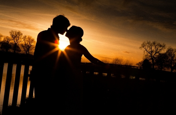 Silhouette of a bride and groom kissing in front of a beautiful sunset - Picture by Jonny Draper Photography