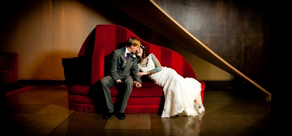 Bride and groom on red sofa - Picture by John Charlton Photography