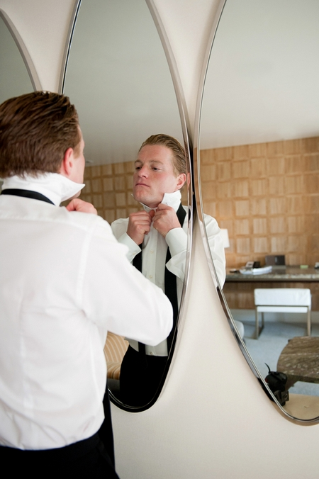 Groom doing up his top button - Picture by Yvette Roman Photography