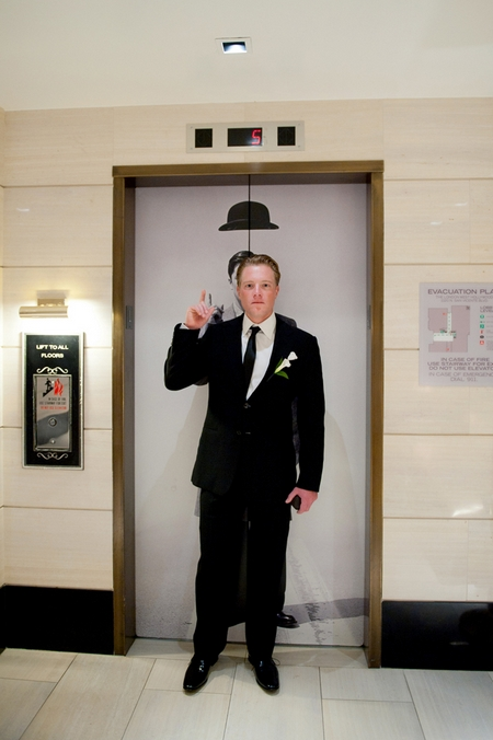 Groom standing in front of a lift with picture of hat above his head - Picture by Yvette Roman Photography