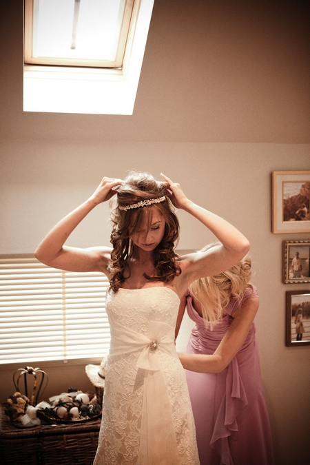 Bridesmaid adjusting bride's dress - Picture by Archibald Photography