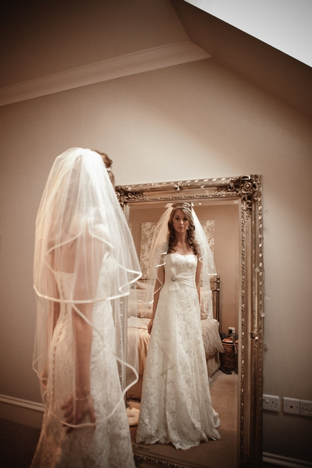 Bride looking at her reflection in mirror - Picture by Archibald Photography
