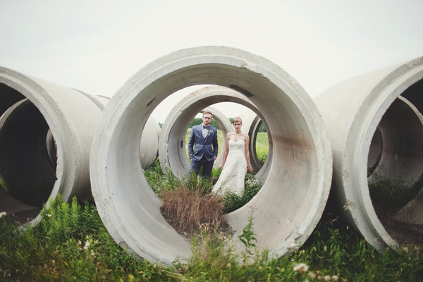 Bride and groom behind concrete cylinders - Picture by Josh Dookhie Photography