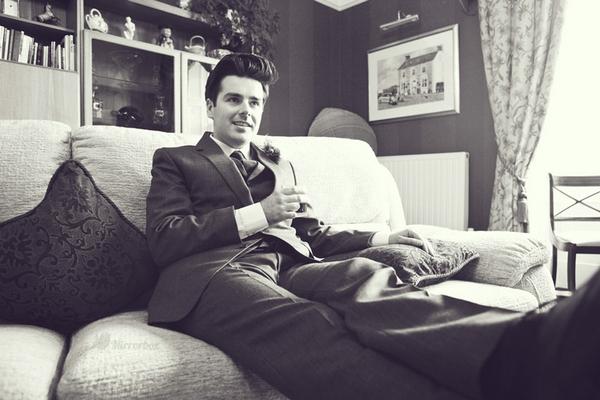 Groom sitting on sofa - Picture by Mirrorbox Photography