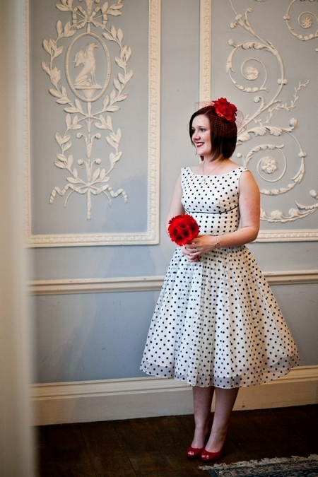 Bride wearing blue polka dot wedding dress holding red bouquet - Picture by Anneli Marinovich Photography