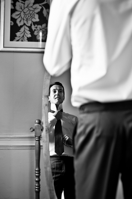Groom adjusting tie in mirror - Picture by Anneli Marinovich Photography