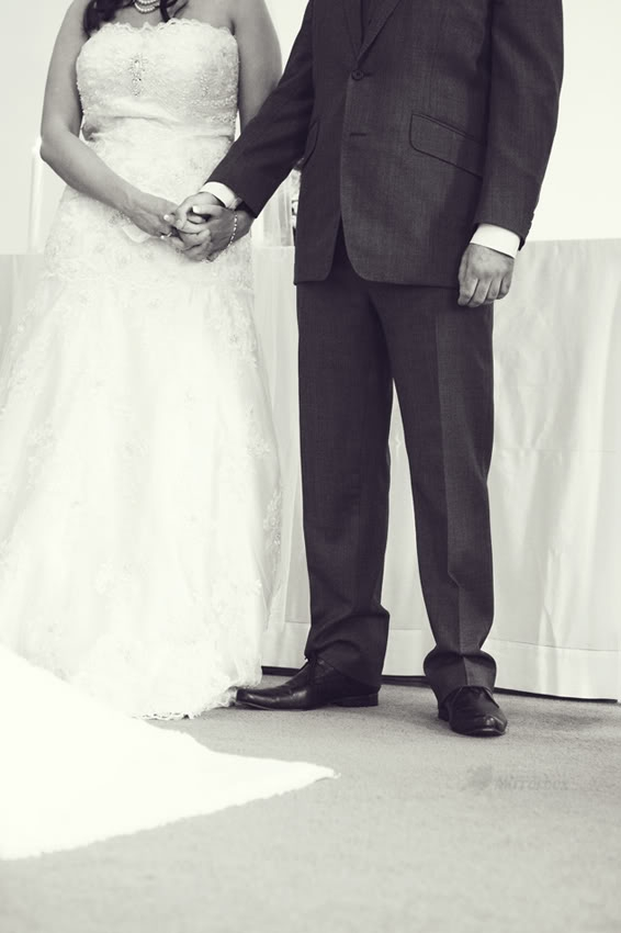 Bride and groom holding hands in church - Picture by Mirrorbox Photography