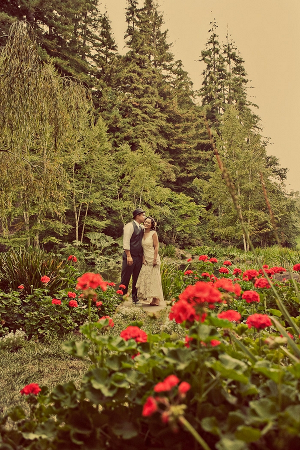 Vintage bride and groom standing amongst red flowers - Picture by Paco and Betty