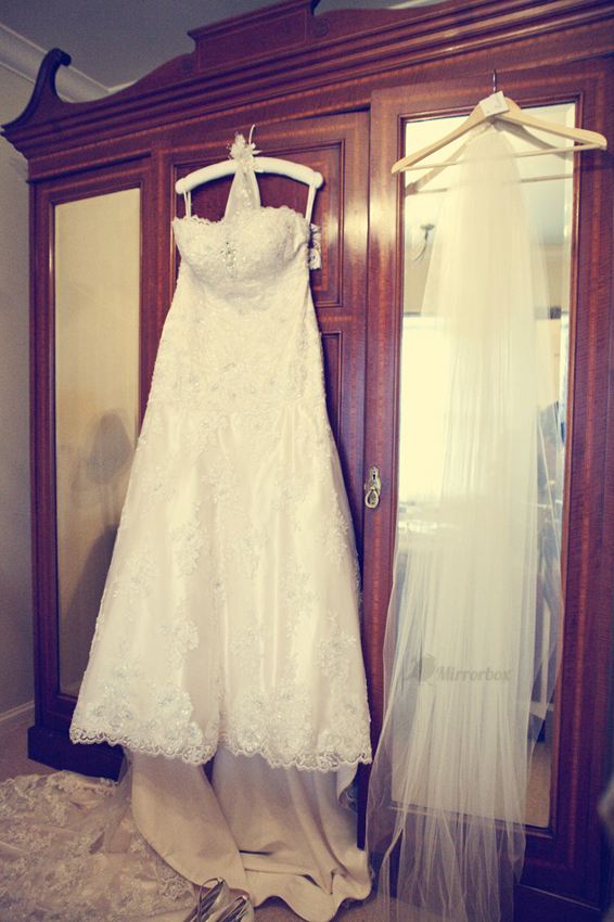 Vintage wedding dress hanging on wardrobe - Picture by Mirrorbox Photography