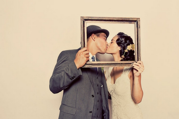 Bride and groom kissing behind picture frame in funbooth - Picture by Paco and Betty