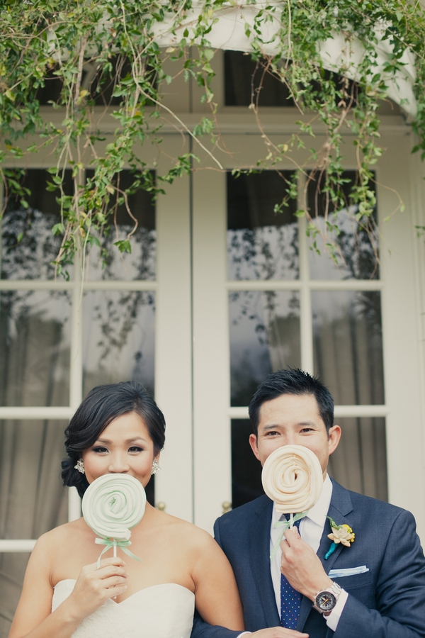 Bride and groom holding lollipops - Picture by onelove photography