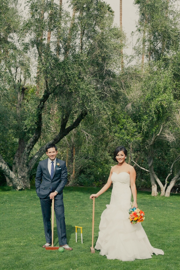 Bride and groom with croquet mallets - Picture by onelove photography