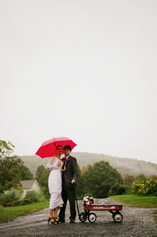 Bride and groom under red umbrella in the rain - Picture by Judy Pak Photography
