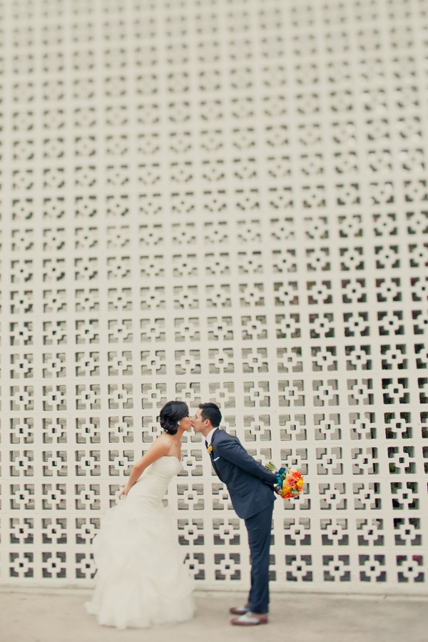 Bride and groom kissing in front of large patterned wall - Picture by onelove photography
