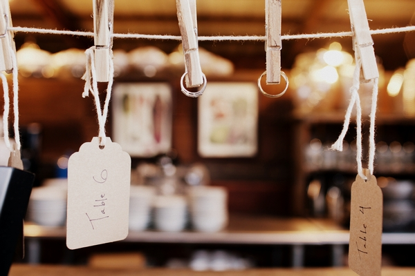 Tags and wedding rings hanging from pegs - Picture by Judy Pak Photography