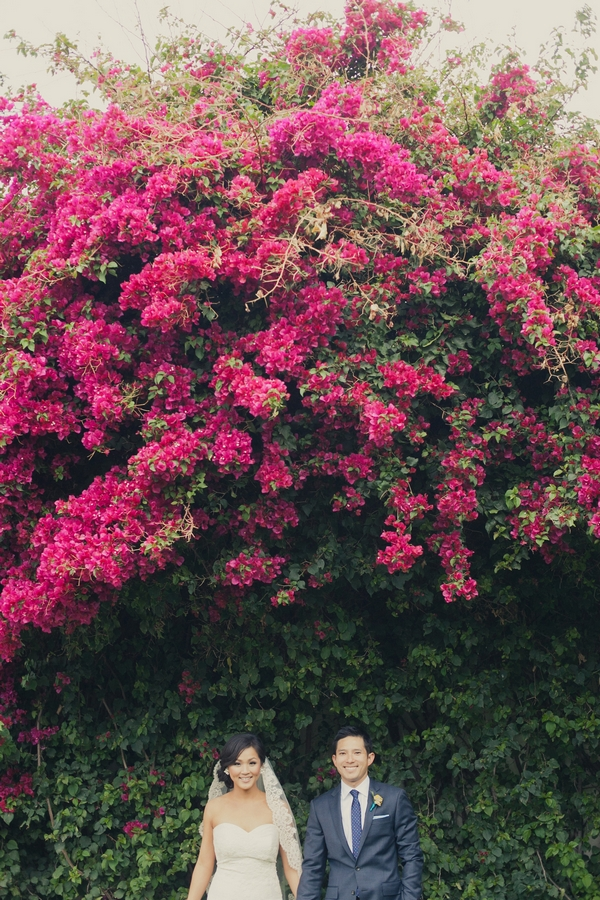 Bride and groom standing under pink flowered tree - Picture by onelove photography
