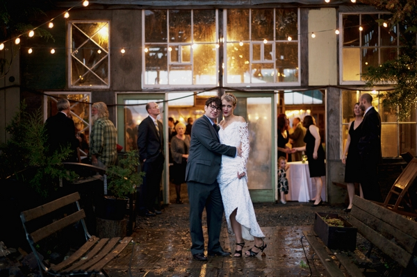 Bride and groom outside barn wedding venue in rain - Picture by Judy Pak Photography