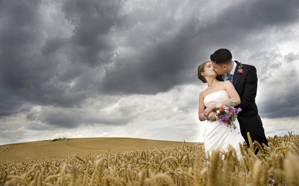 Bride and groom kissing in a field with dark clouds overhead - Picture by Charlotte Snowden Photography