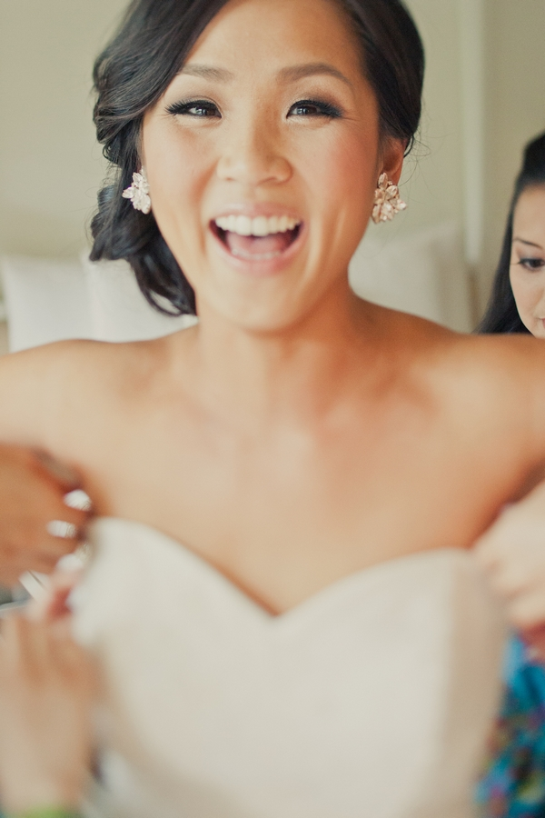 Bride putting on wedding dress - Picture by onelove photography