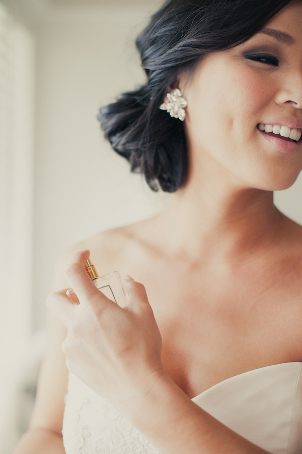 Bride putting on perfume - Picture by onelove photography