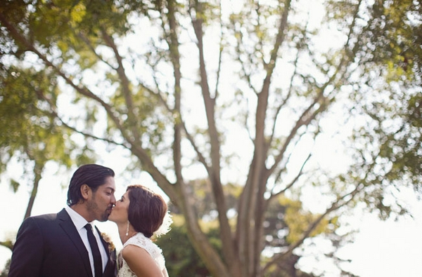 Bride and groom kissing in front of tree branches - Picture by Joielala