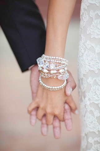 Close up of bride and groom holding hands - Picture by Joielala
