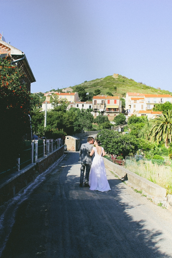 Back of bride and groom walking through streets of Cargese - Picture by DanielRM