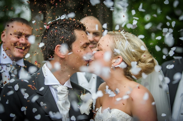 Bride and groom kissing during confetti shower - Picture by Pixies in the Cellar