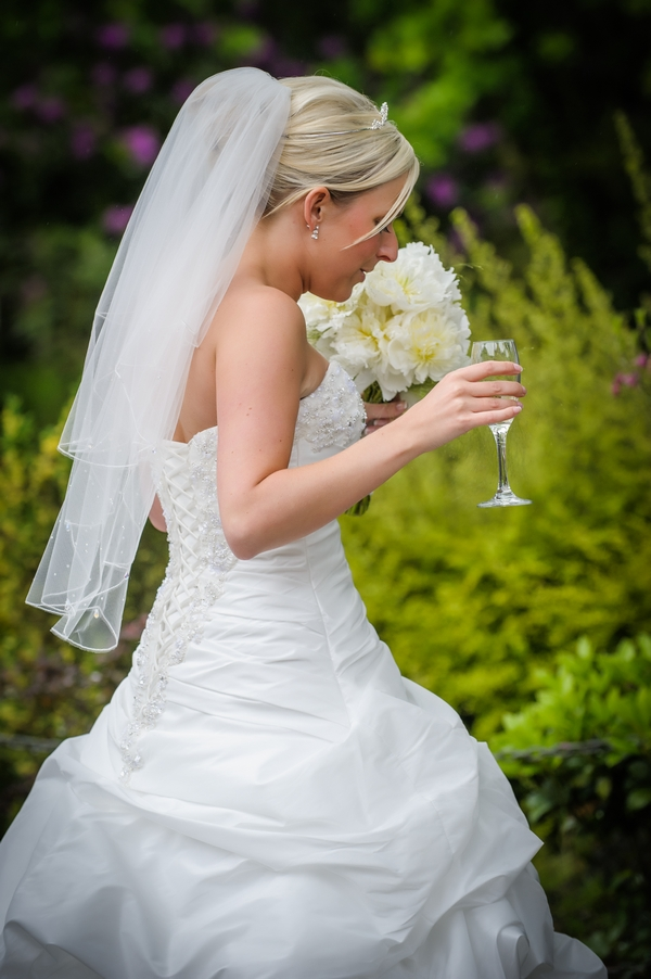 Bride carrying bouquet and glass of Champagne - Picture by Pixies in the Cellar