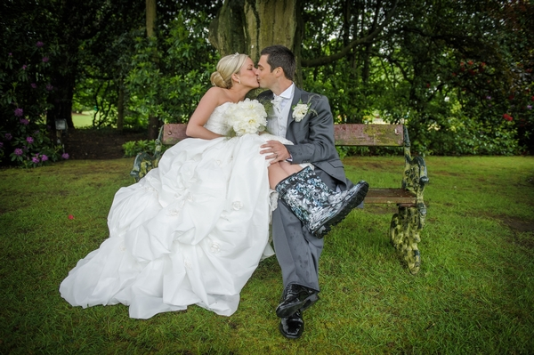 Groom kissing bride in wellies on bench - Picture by Pixies in the Cellar