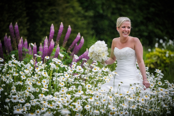 Bride standing in field of flowers - Picture by Pixies in the Cellar