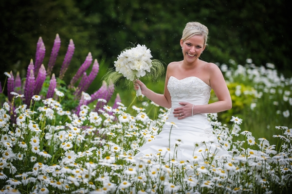 Bride holding bouquet in field of flowers - Picture by Pixies in the Cellar